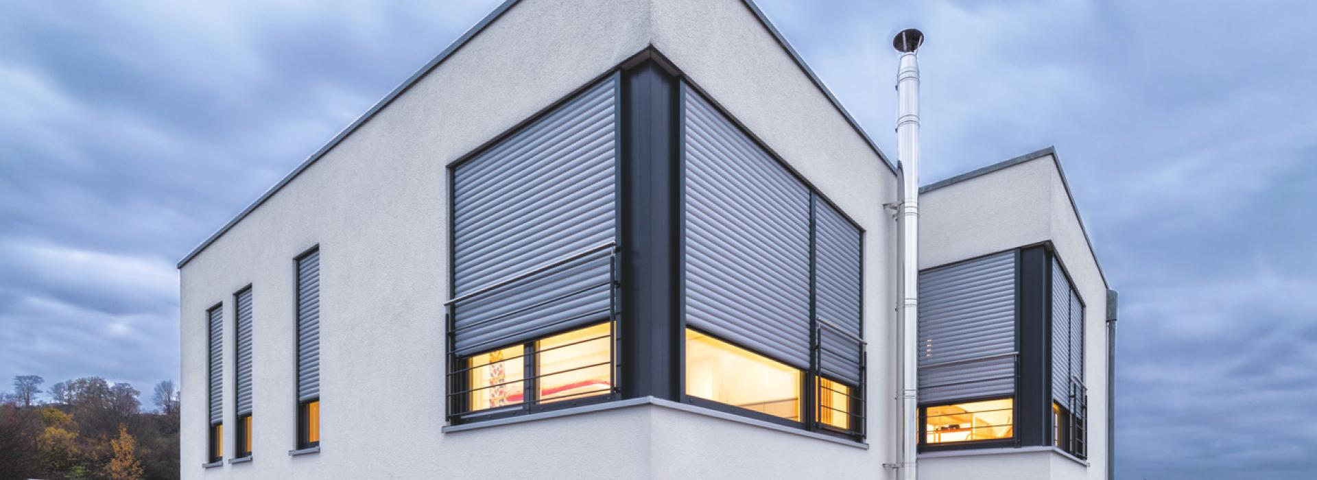 Single-family home detailed view window with nearly closed roller shutters
