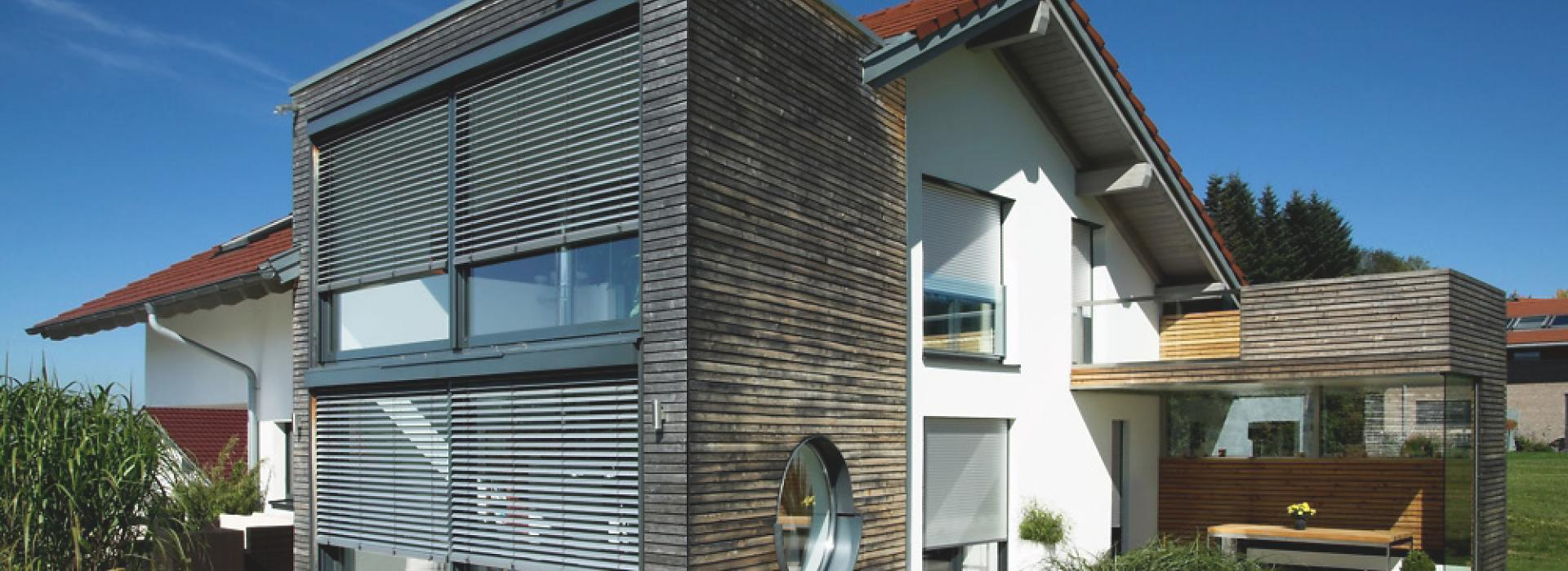 Wooden construction of house with front-mounted external venetian blinds by daylight