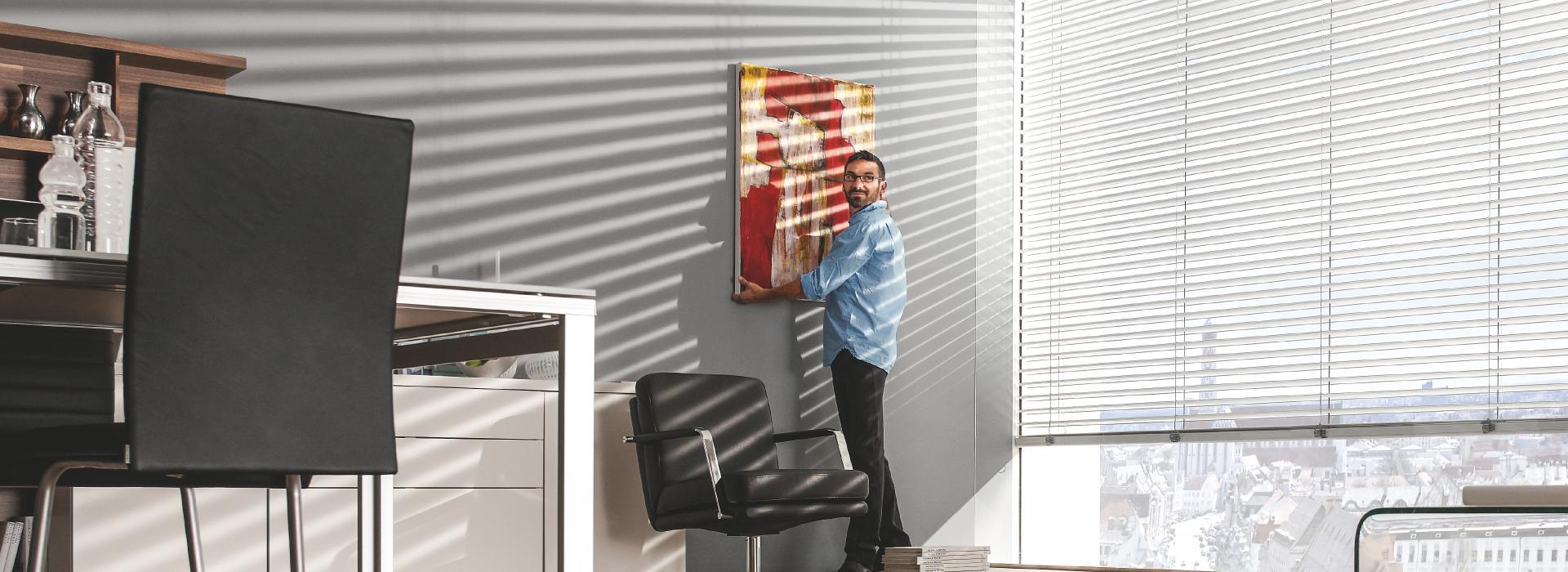 Man hangs up painting in office, external venetian blinds are tilted