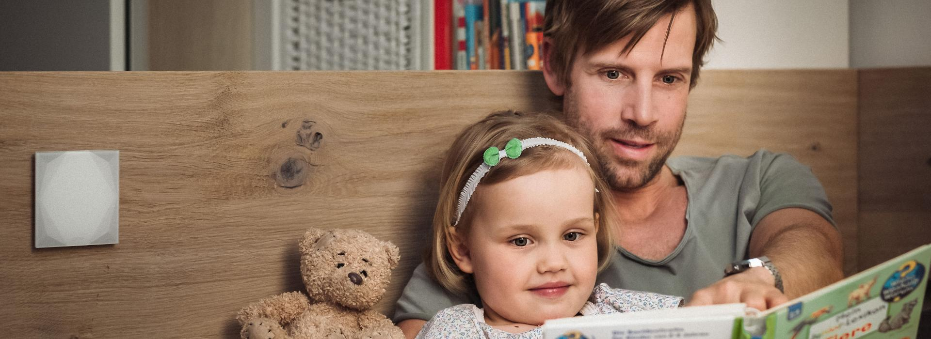 Father sits in bed with his daughter reading a book