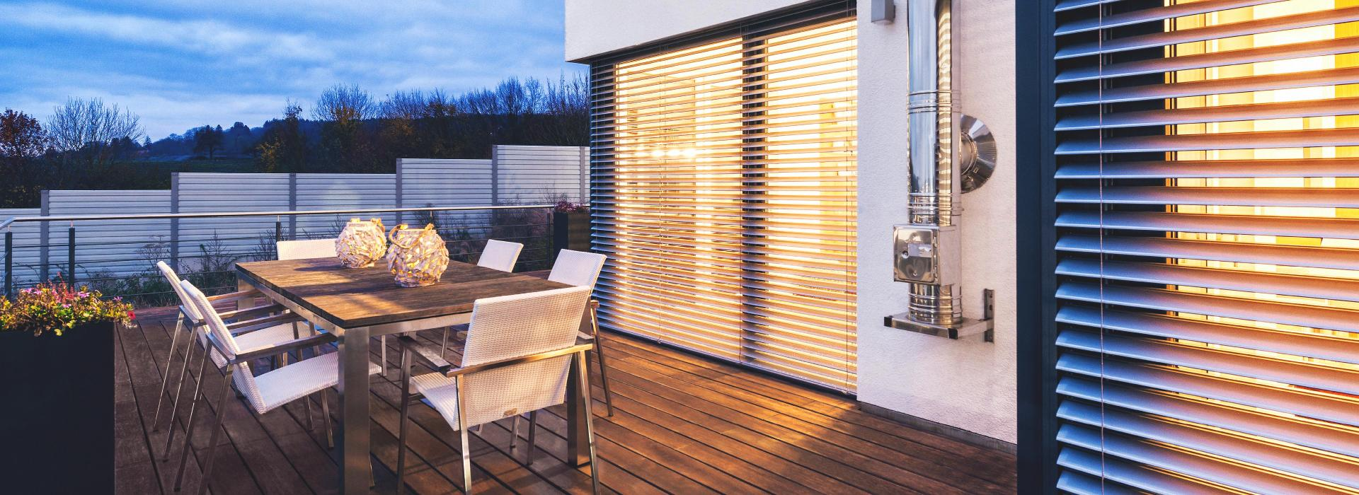 Patio with seating area in the twilight and with view to ROMA half opened external venetian blinds